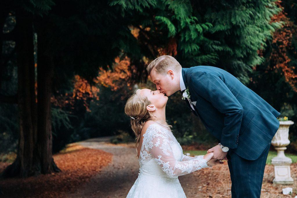 Groom kissing the Bride on the drive way of Eshott Hall, Northumberland