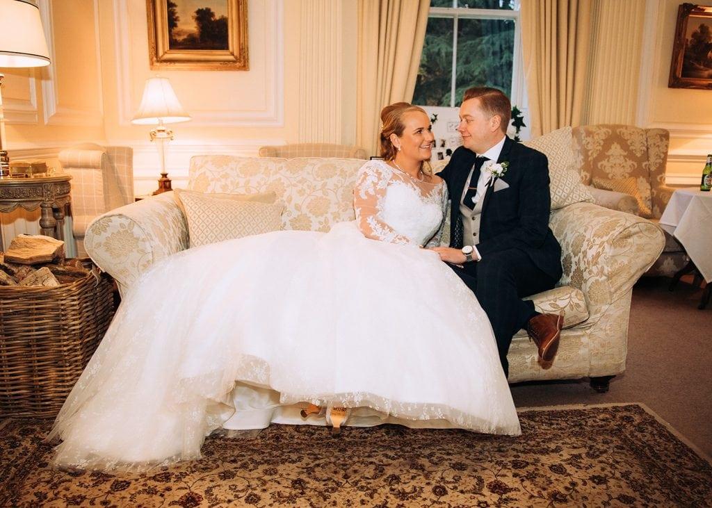 Bride and Groom relaxing on the sofa's of Eshott Hall, Northumberland