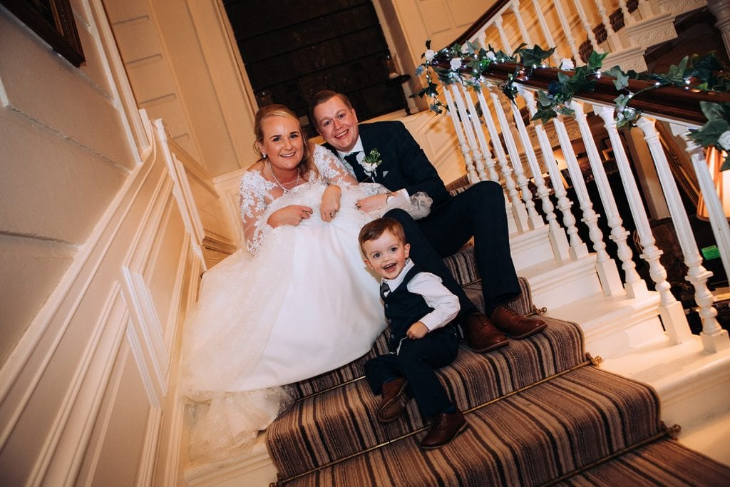 Bride & Groom playing with their page boy on the stairs of Eshott Hall, Northumberland