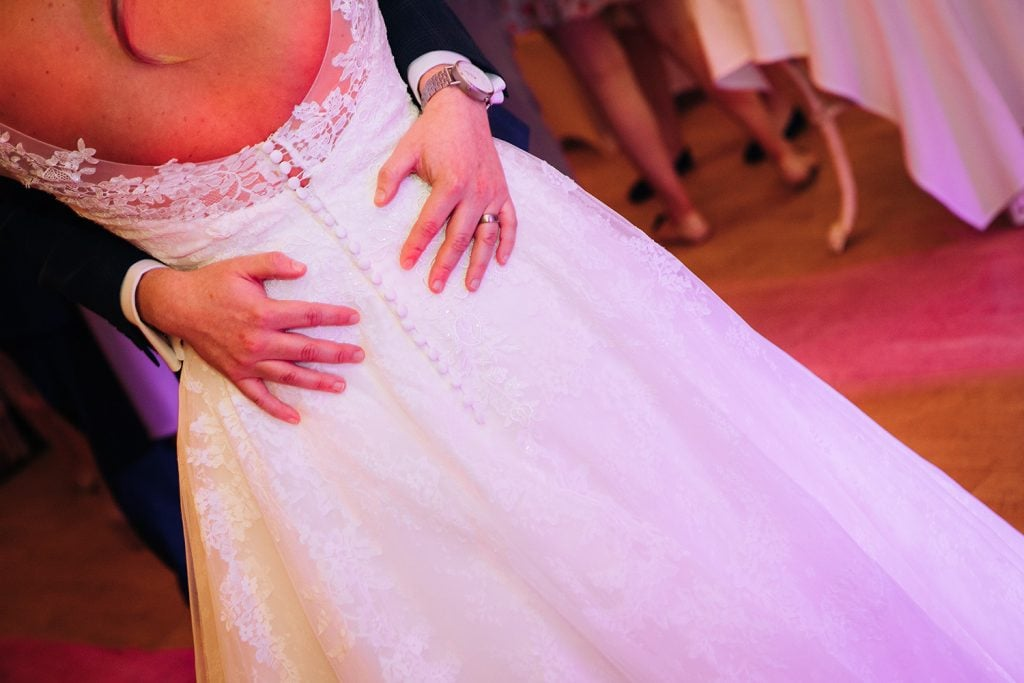 Grooms hands & the back of brides dress at Eshott Hall, Northumberland