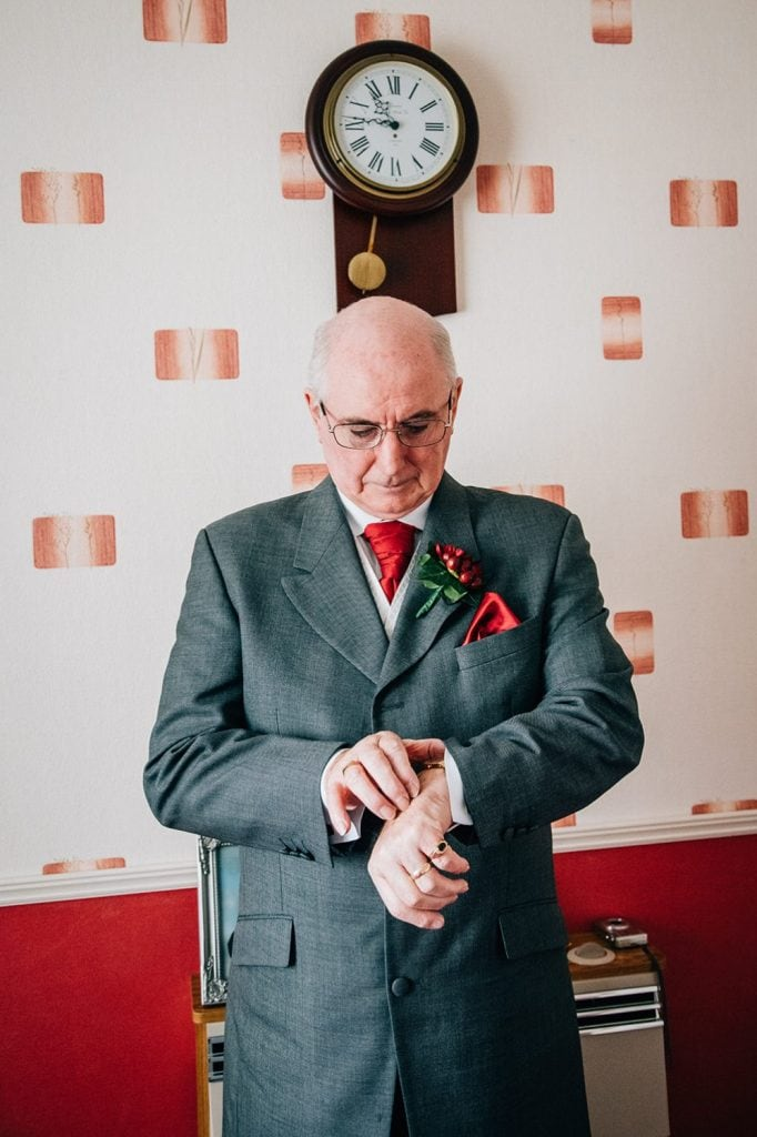Father of the Bride Checking his Watch with a Wall Clock behind him