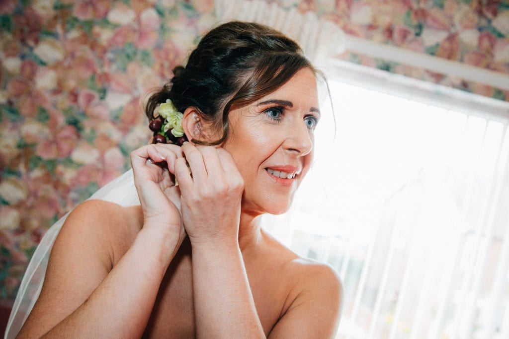 Bride putting earing in