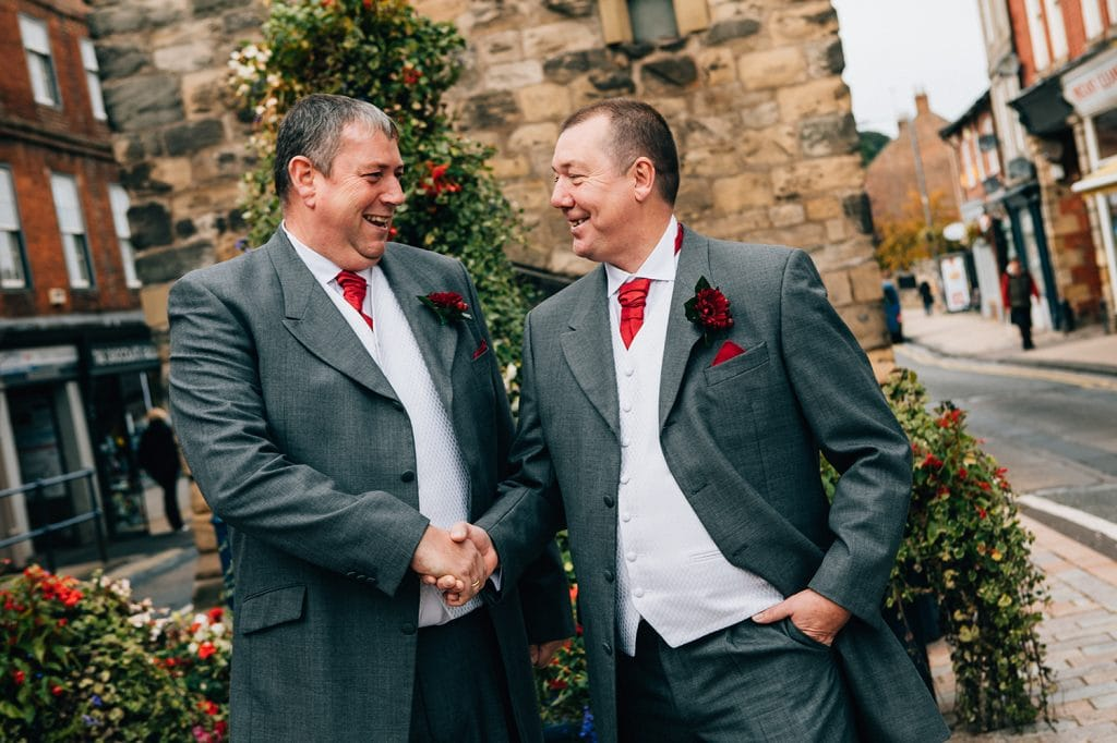 Groom shaking best man hand outside the clock tower in Morpeth, Northumberland