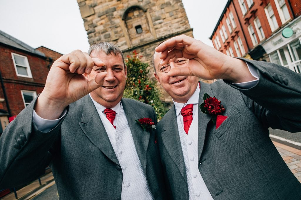 Groom & Best man looking through the wedding rings outside the clock tower in Morpeth, Northumberland