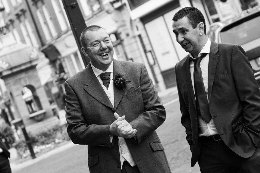 Groom laughing with his friend outside Morpeth Town Hall