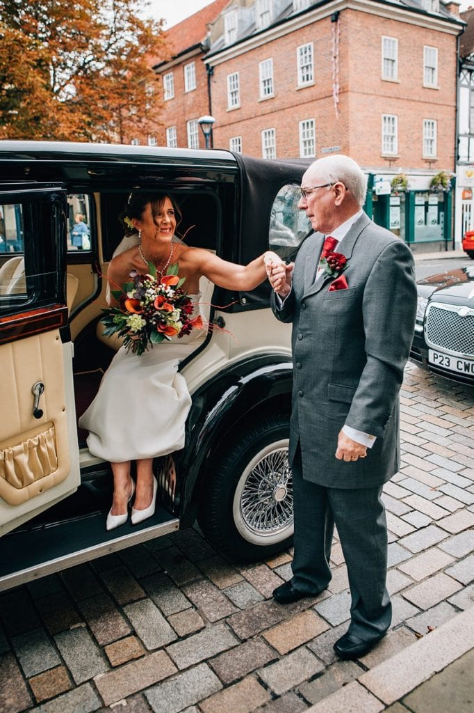Brides father helping her out of their vintage wedding car
