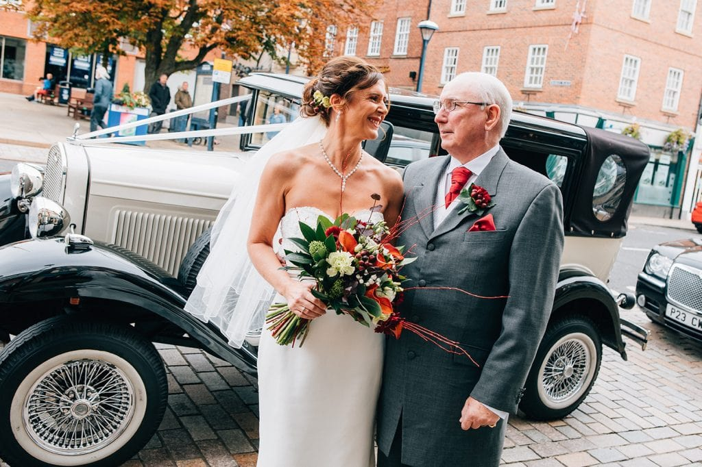 Bride with her dad in front of their vintage wedding car outside Morpeth Town Hall