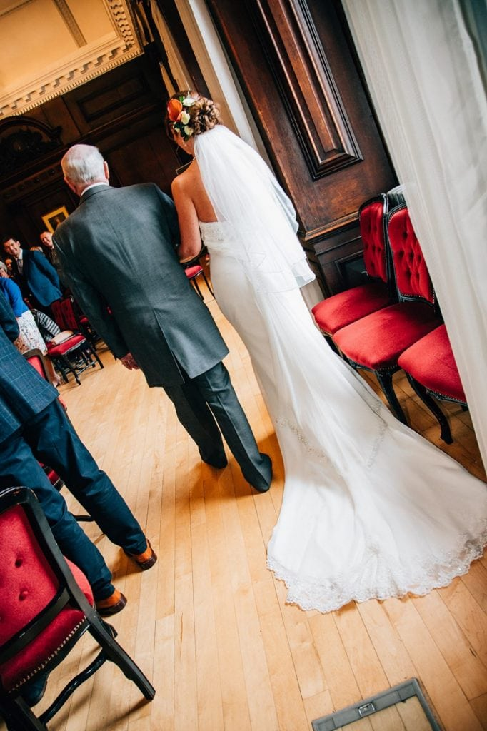 Rear view of brides dress as she walks down the aisle in the Ballroom, Morpeth Town Hall