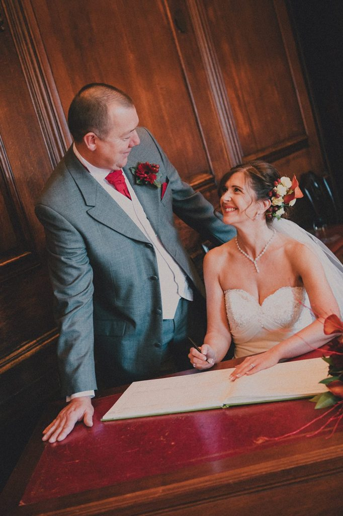 Bride & Groom looking at each other while signing the register in the Ballroom, Morpeth Town Hall
