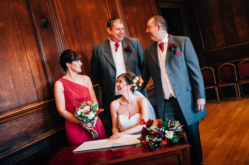 The witnessess talking to the bride & groom while signing the register in the Ballroom, Morpeth Town Hall