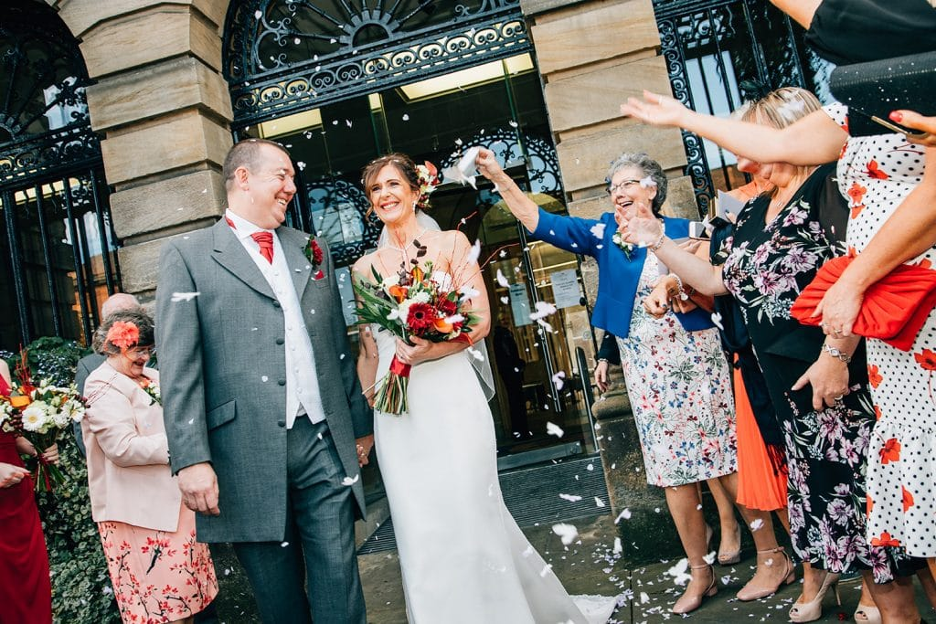 Bride & Groom covered in confetti outside of Morpeth Town Hall
