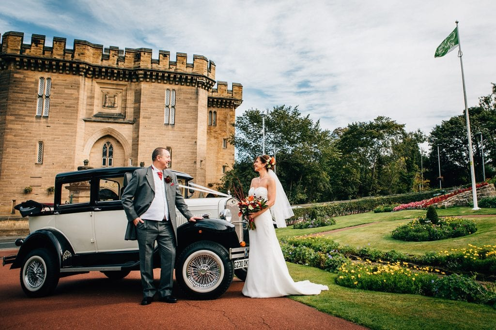Bride & Groom next to their vintage wedding car at Carlisle Park, Morpeth before the Waterford Lodge Hotel