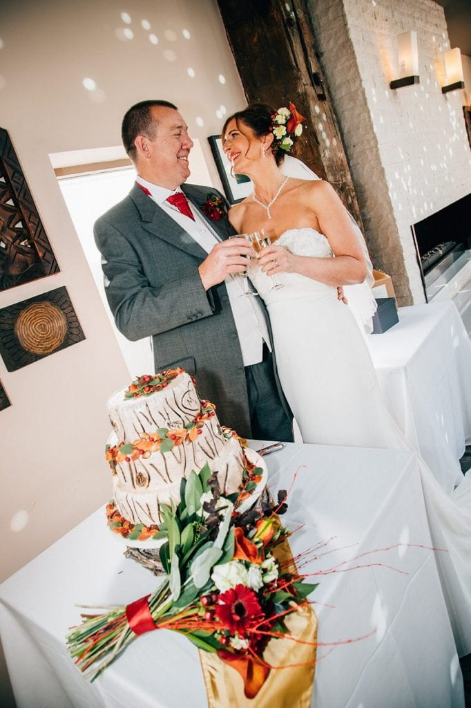 Bride & Groom toasting next to their wedding cake at The Waterford Lodge in Morpeth
