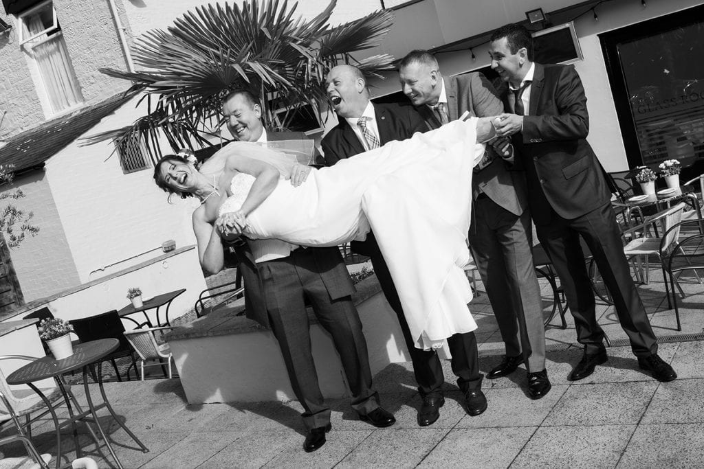 Bride being held by groom and his friends at The Waterford Lodge in Morpeth