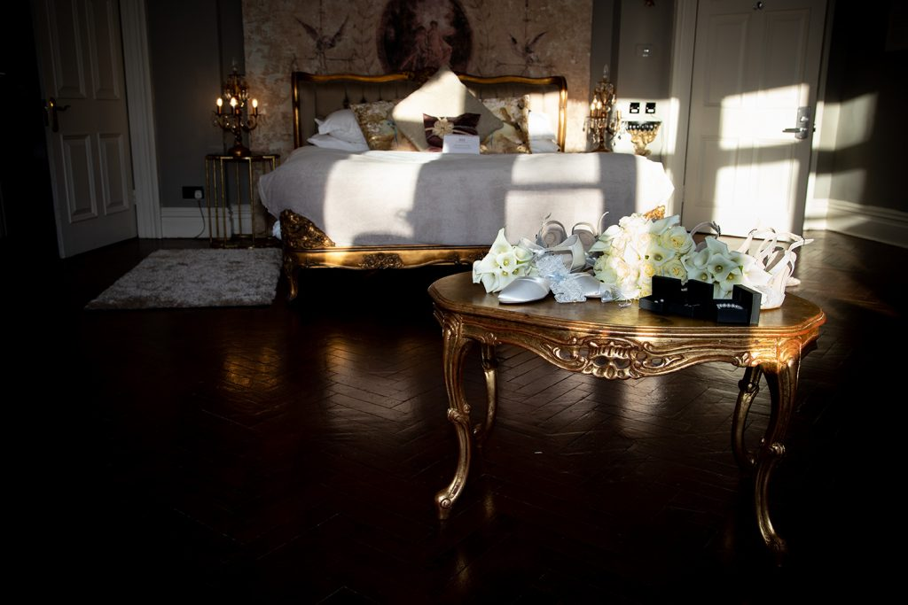 Brides room, flowers and shoes in the sunlight at Ellingham Hall in Northumberland