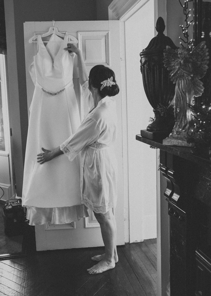 Bridehanging her dress at Ellingham Hall in Northumberland