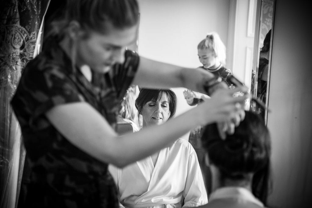 Brides reflection in the mirror as she gets her hair styled