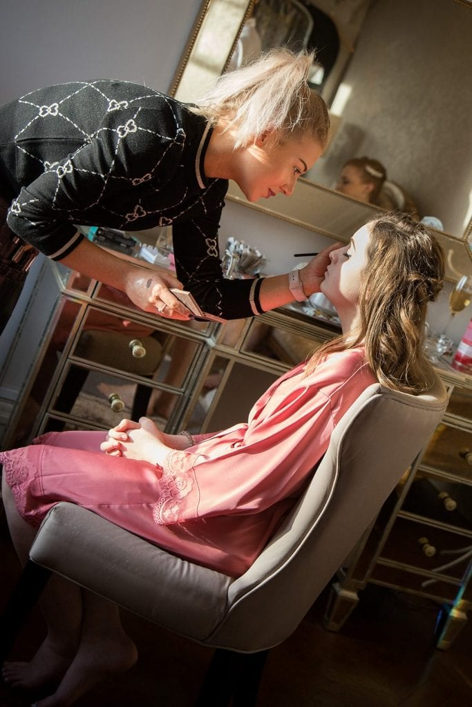 Bridesmaid getting makeup applied at Ellingham Hall in Northumberland