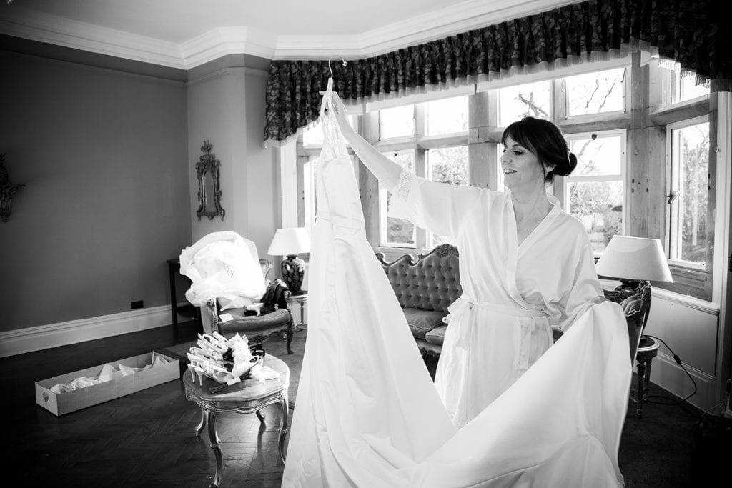 Bride admiring her dress at Ellingham Hall in Northumberland