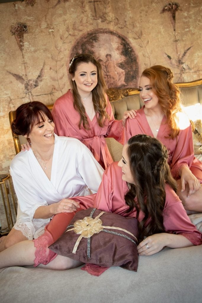 Girls laughing on the brides bed at Ellingham Hall in Northumberland