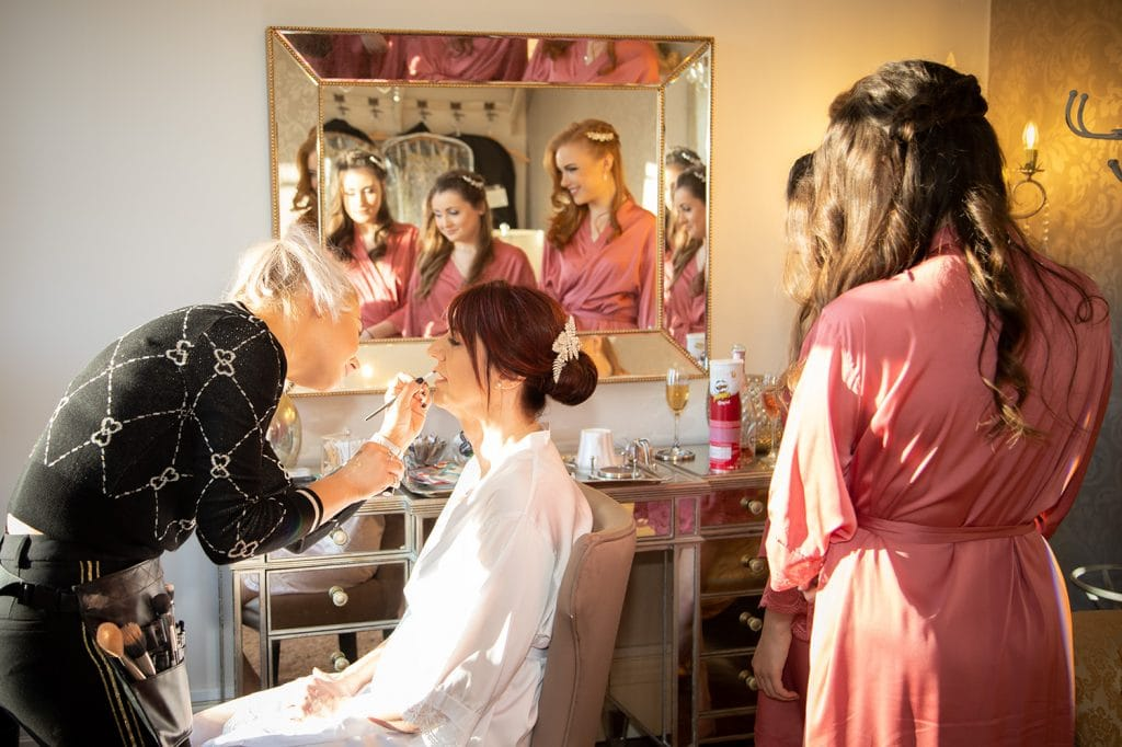 bridesmaids watching the bride get her makeup done at Ellingham Hall in Northumberland