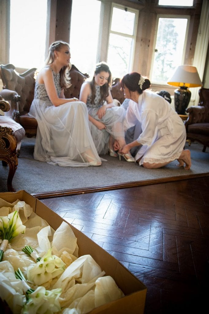 Bride helping bridesmaids get ready in Ellingham Hall in Northumberland