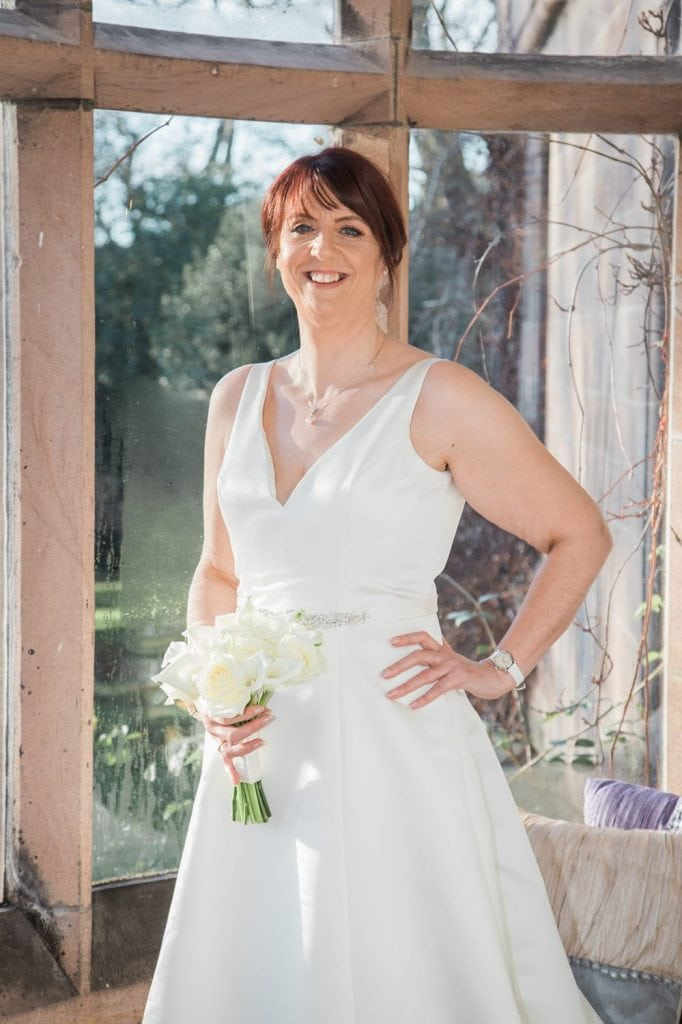 The bride posing in her room at Ellingham Hall in Northumberland