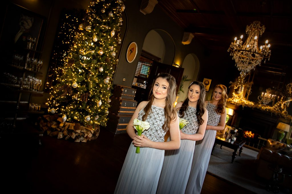 Bridesmaids waiting nest to christmas decorations at Ellingham Hall in Northumberland