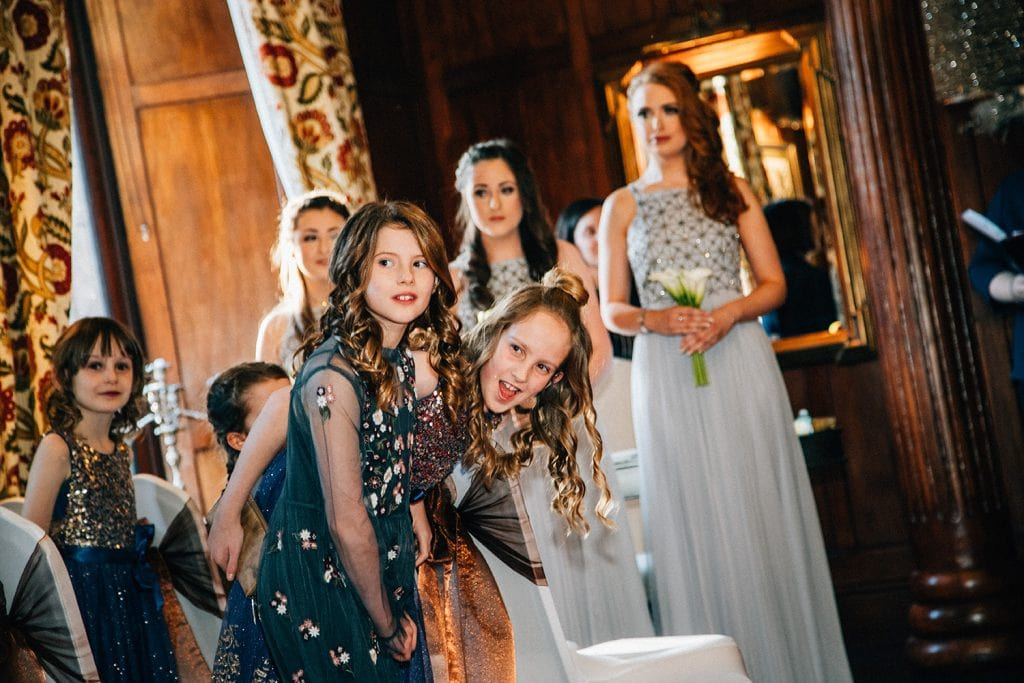 Girls watching the bride walk down the aisle inside Ellingham Hall in Northumberland