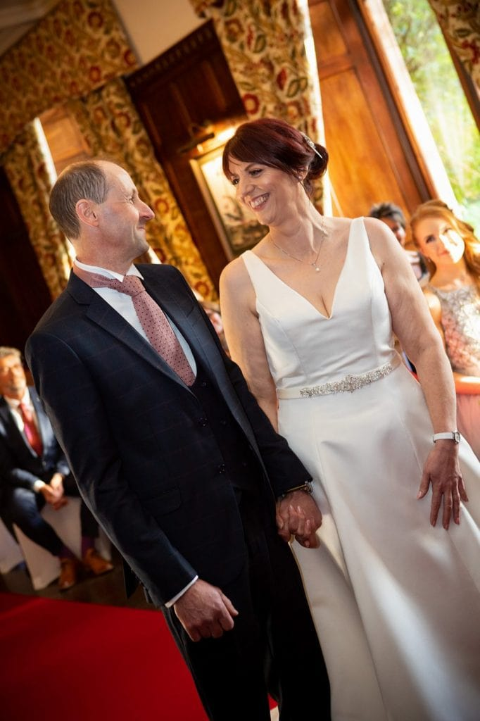 Bride & groom smiling at each other at Ellingham Hall in Northumberland