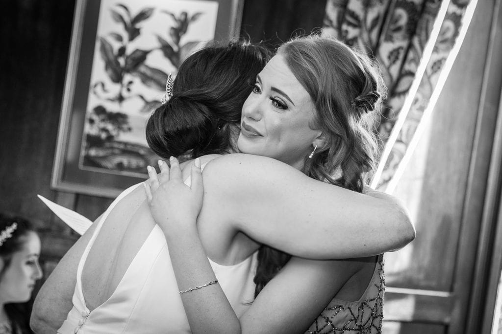 Bride hugging crying bridesmaid