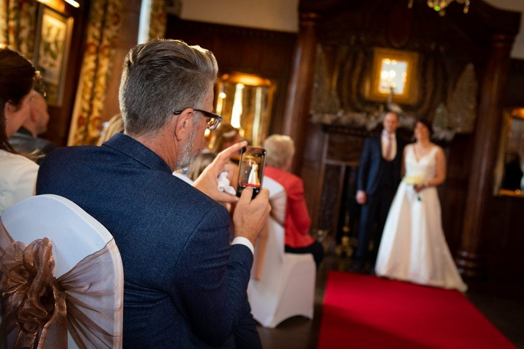 A guest photographing the bride & groom