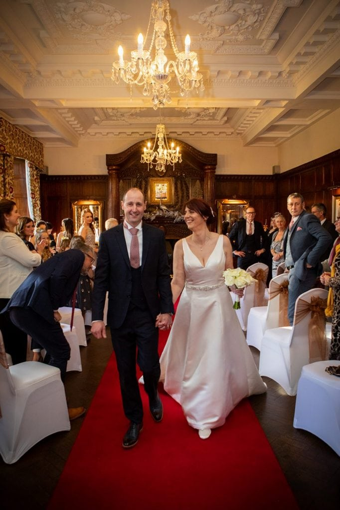 The newly wedded couple walking down the aisle at Ellingham Hall in Northumberland