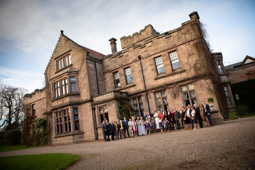 A group shot of all guests in front of Ellingham Hall in Northumberland
