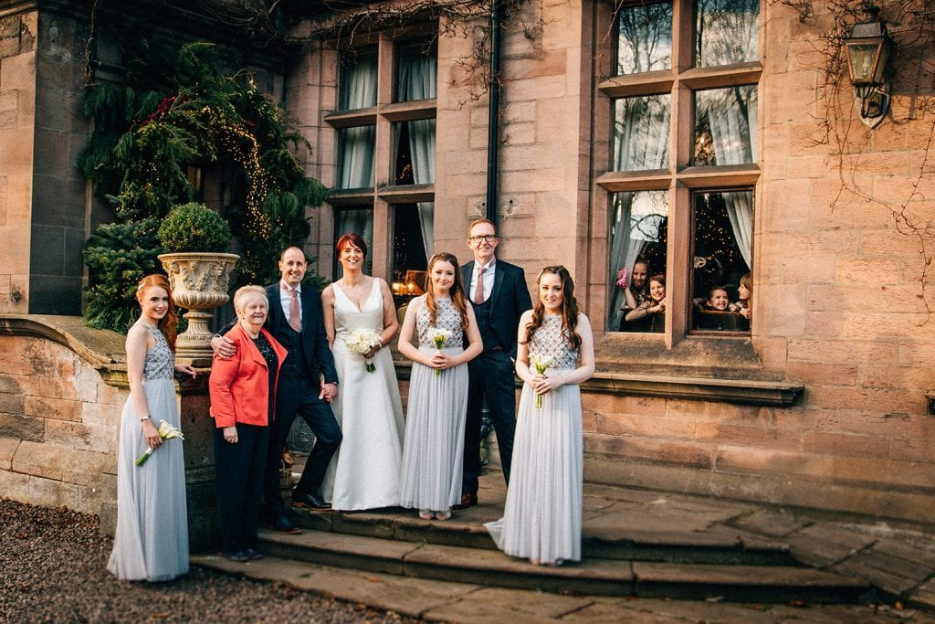 The bridal party being watched from the window outside Ellingham Hall in Northumberland