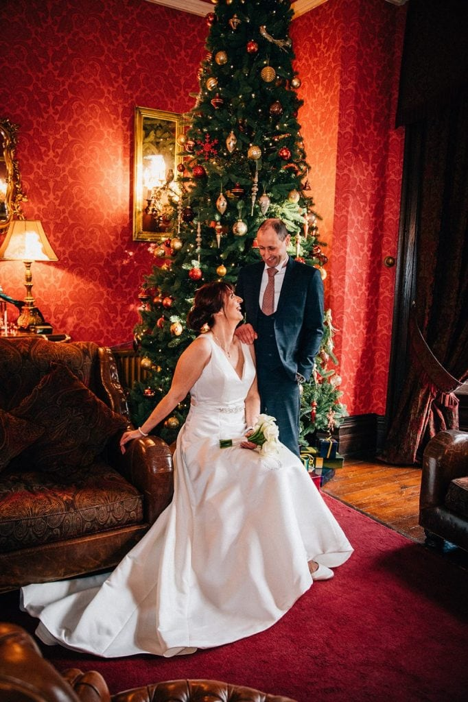 The bride & groom enjoying the christmas decorations at Ellingham Hall in Northumberland