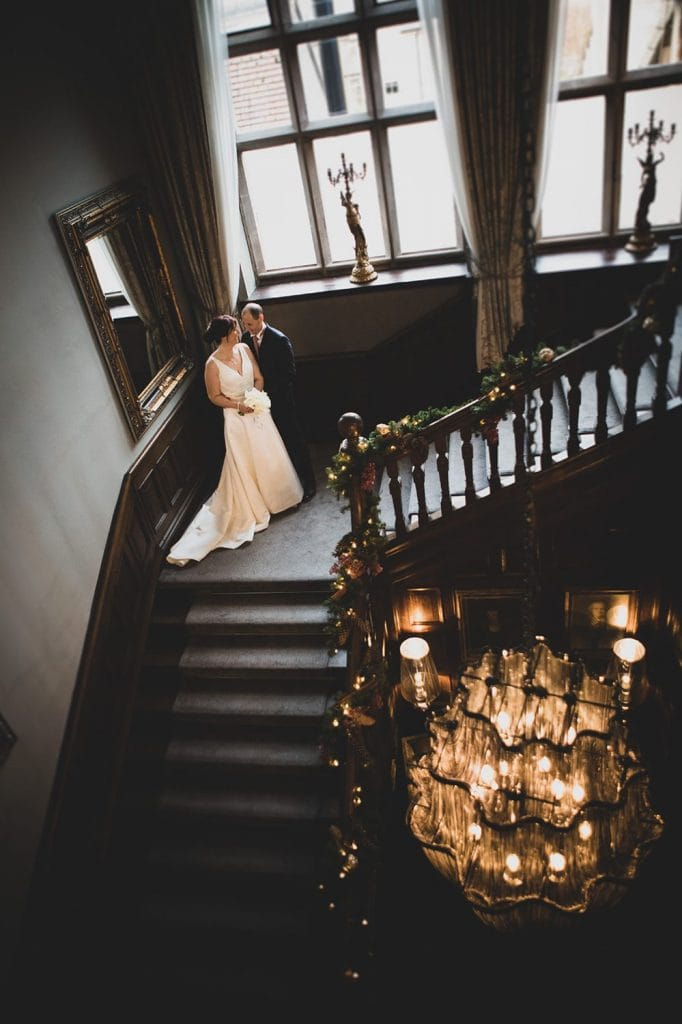 The bride & groom on the staircase of Ellingham Hall in Northumberland