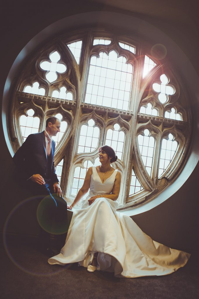 The bride and groom in the chapel window of Ellingham Hall in Northumberland