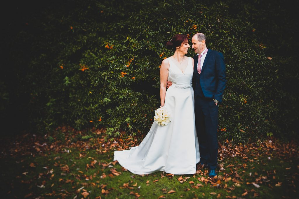 The bride & groom cuddling in the grounds