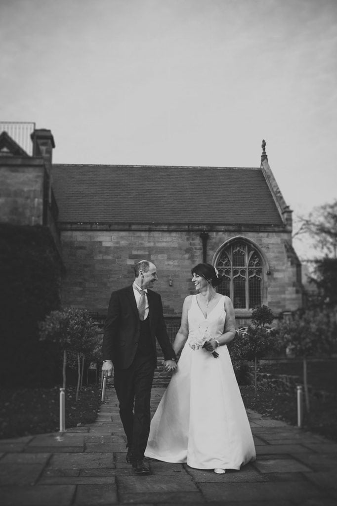 The bride & groom walking throught the grounds at Ellingham Hall in Northumberland