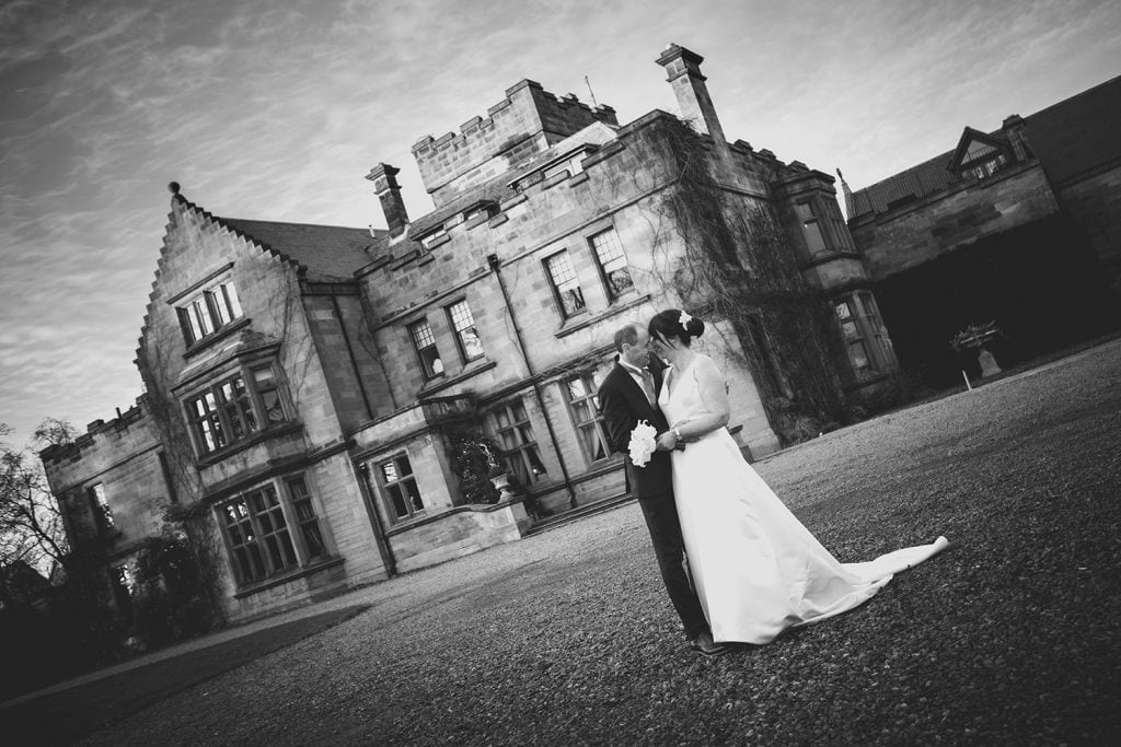 The bride & groom facing each other at Ellingham Hall in Northumberland