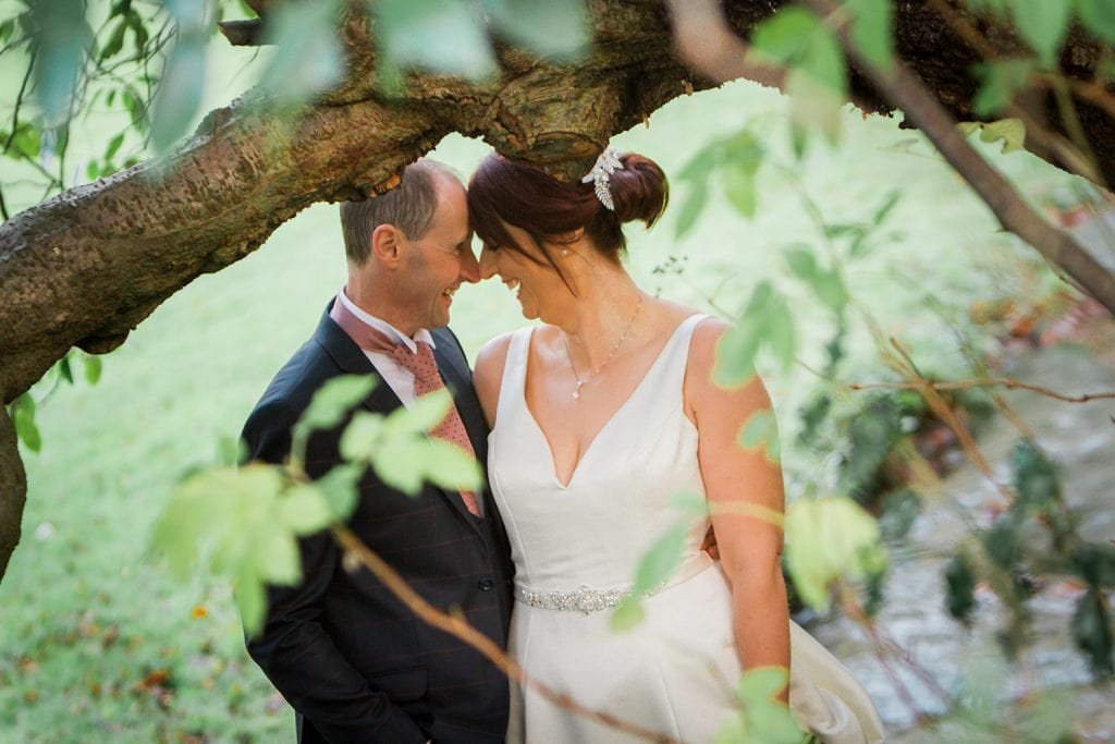 The bride & grrom nose to nose in the woods