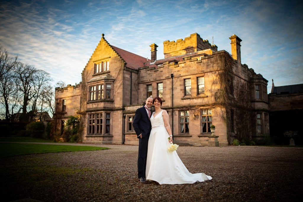 The bride & groom in front of Ellingham Hall in Northumberland