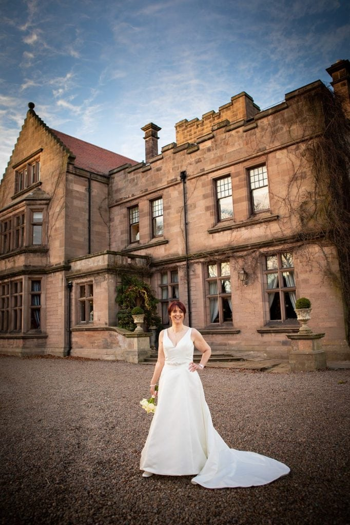 The bride in front of Ellingham Hall in Northumberland