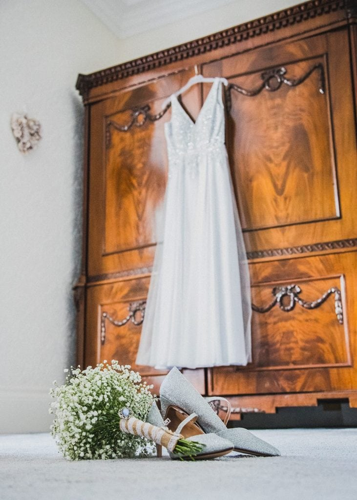 Brides shoes and bouqeut in front of the wedding dress
