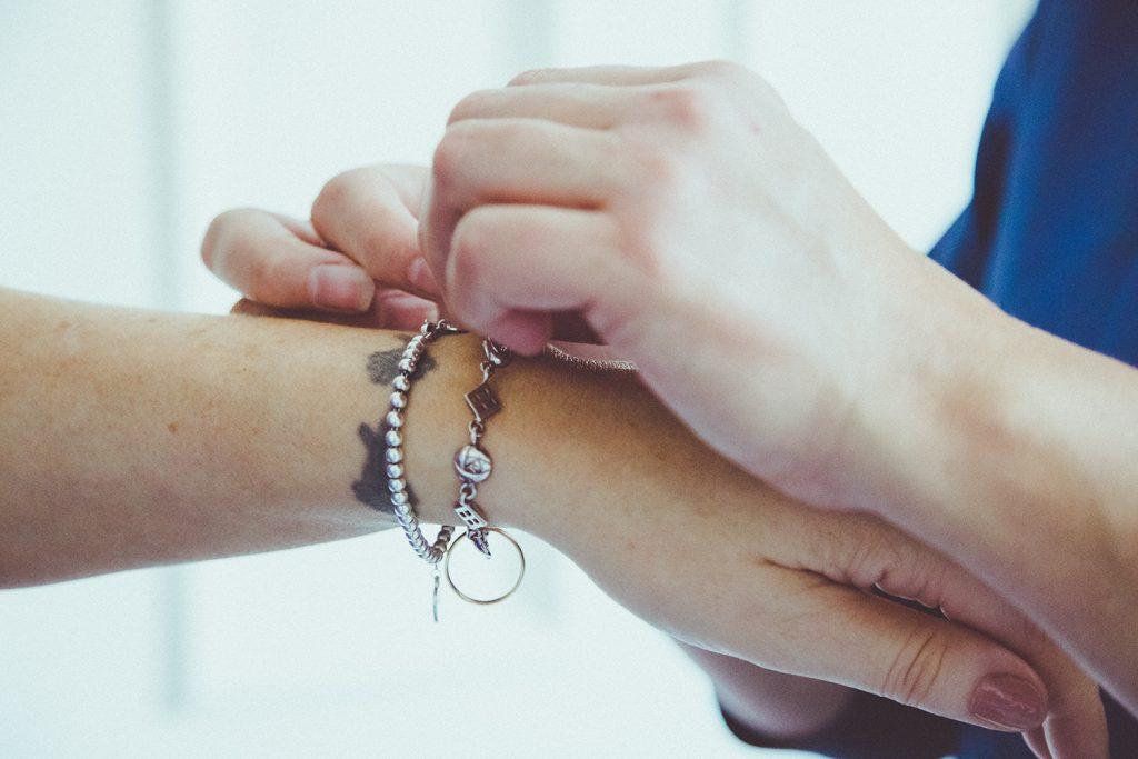 Close up of bridesmaid fastening brides bracelet