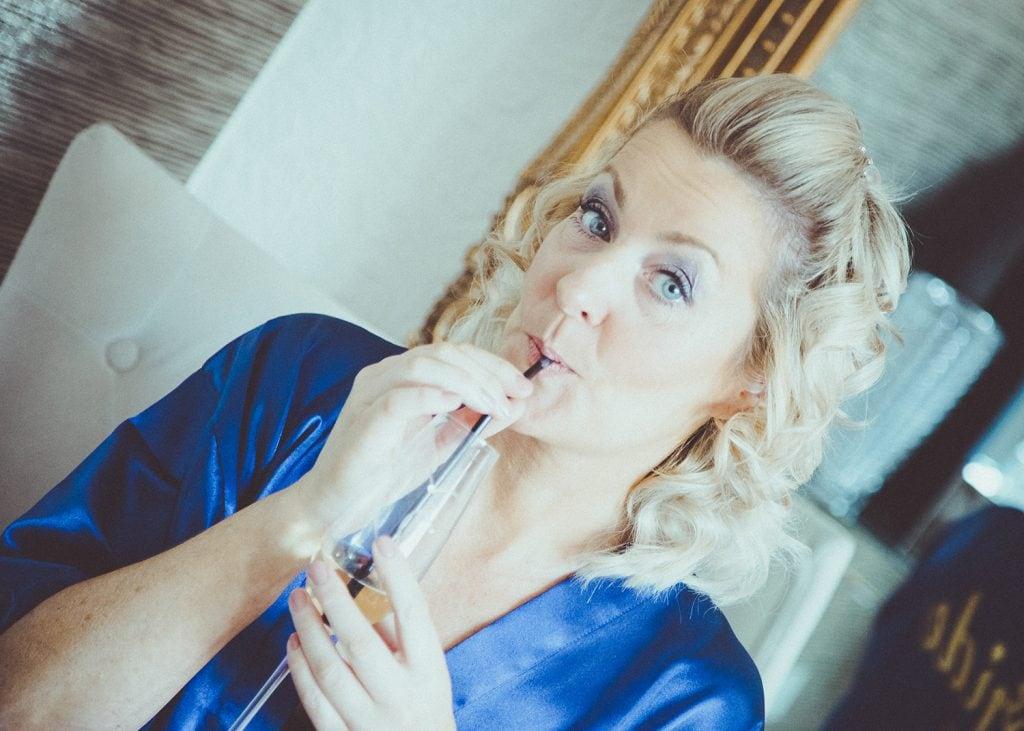 Bride drinking champayne through a straw