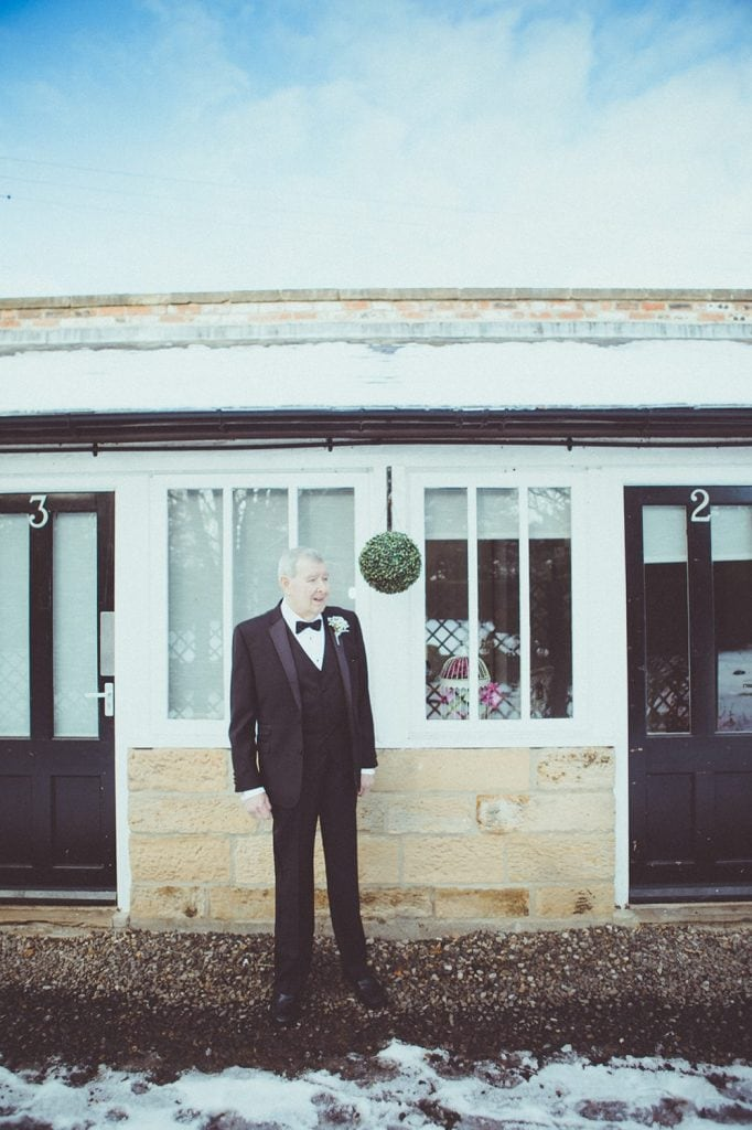 Father of the bride waiting in the snow at Horton Grange Hotel in Northumberland
