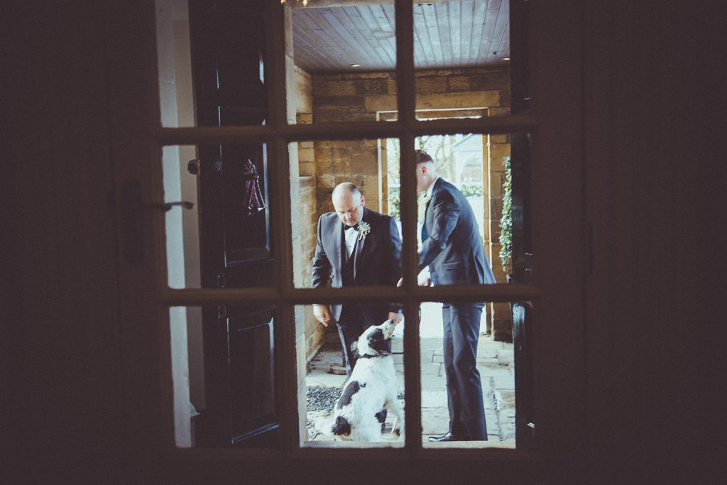 Groom with his Spaniel through the door of Horton Grange Hotel in Northumberland
