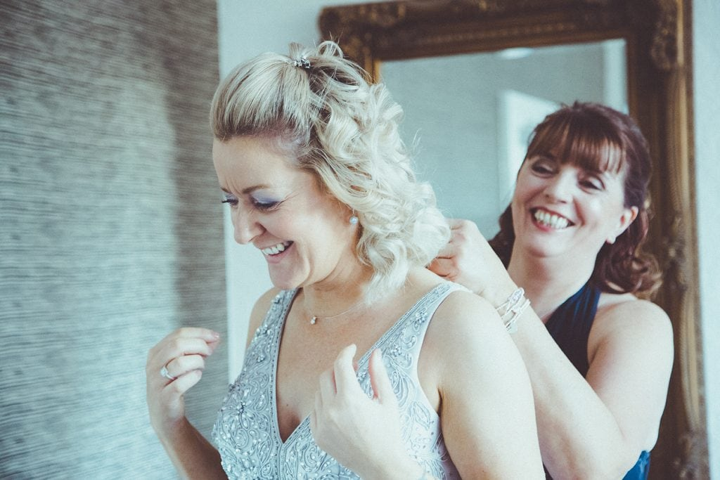 Maid of honor helping the bride with her necklace